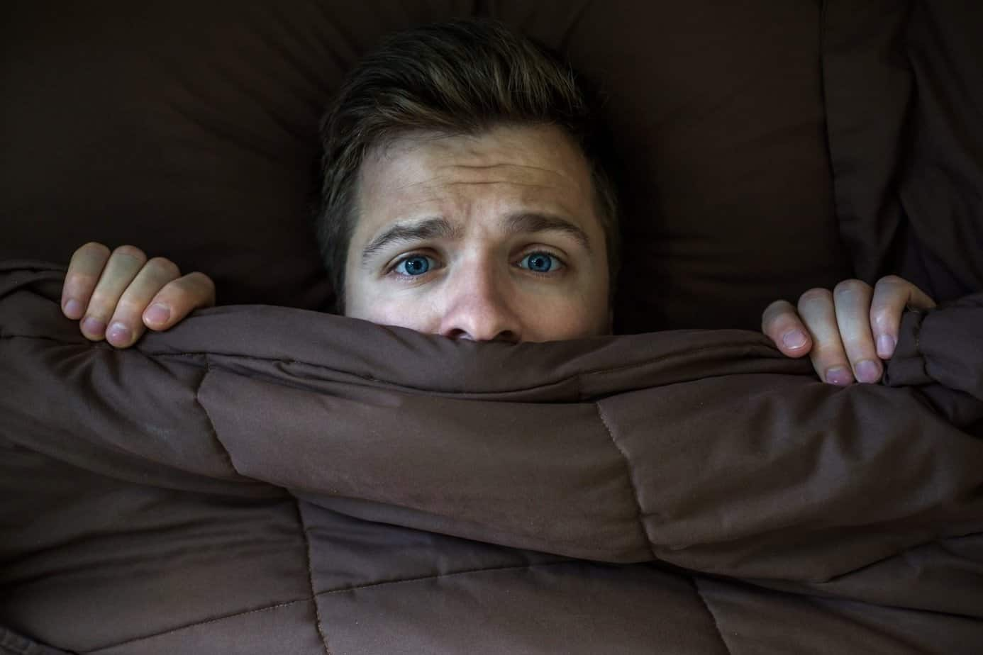 Man in bed having anxious thoughts